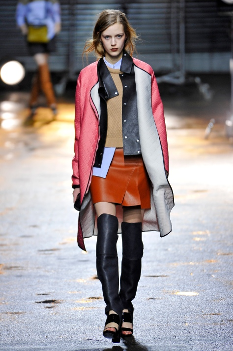 Phillip Lim, Coat: Grapefruit embossed neoprene overcoat with detachable leather bib; Pullover: Camel roll neck cropped pullover; Shirt: Blue pinstripe cropped sleeveless shirt; Skirt: Cognac leather layered mini skirt; Shoes: Black 'Ora' over the knee boot sandal, Fall 2013